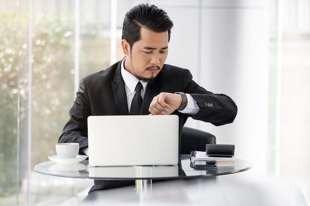 Biznesowy mężczyzna sprawdza czas na mądrze zegarku podczas gdy używać laptop