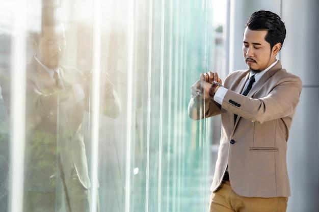 Biznesowy mężczyzna sprawdza czas na mądrze zegarku w biurze