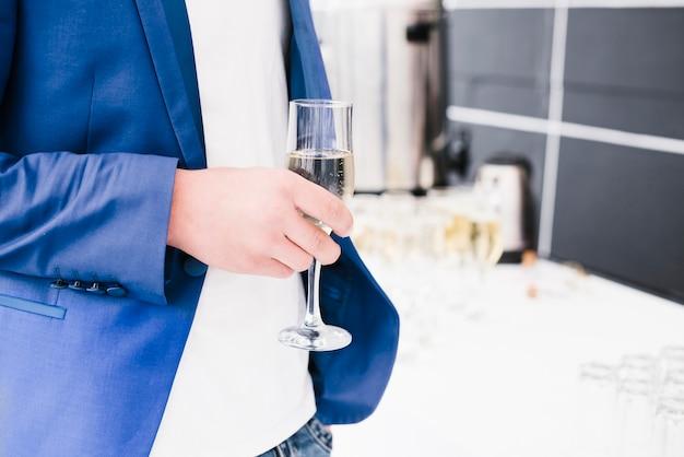 Biznesowy mężczyzna trzyma filiżankę szampana