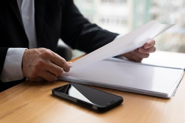 Biznesowy mężczyzna trzyma glansowanego papier