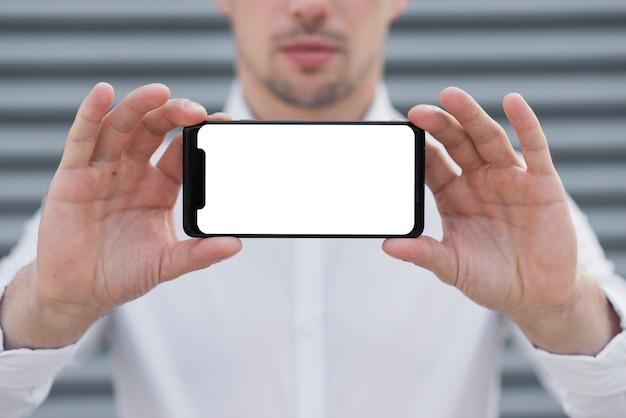 Biznesowy mężczyzna trzyma iphone egzamin próbny