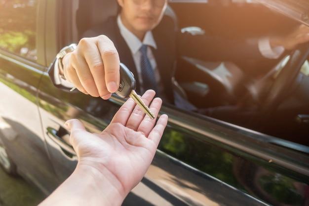 Biznesowy mężczyzna trzyma kluczowego samochód w samochodzie