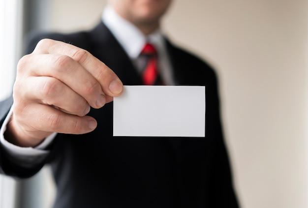 Biznesowy mężczyzna trzyma pustą wizytówkę