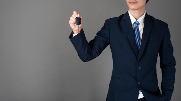 Biznesowy mężczyzna trzyma samochodu klucz, szary tło w studiu