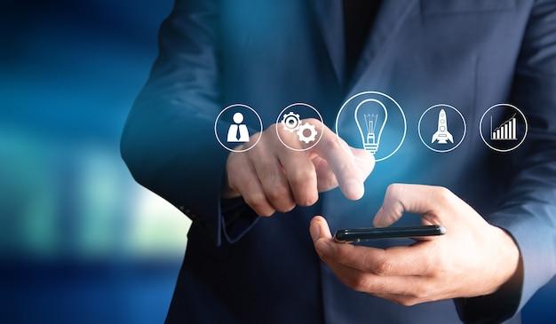 Biznesowy mężczyzna trzyma telefon z ikony uruchamiania