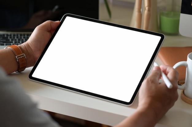 Biznesowy mężczyzna używa cyfrową pastylkę na obszarze roboczym