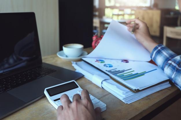 Biznesowy mężczyzna używa kalkulatora przeglądać bilans rocznego z mienia piórem i używać laptop