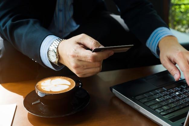 Biznesowy mężczyzna używa kredytową kartę kupować online rzeczy w sklep z kawą
