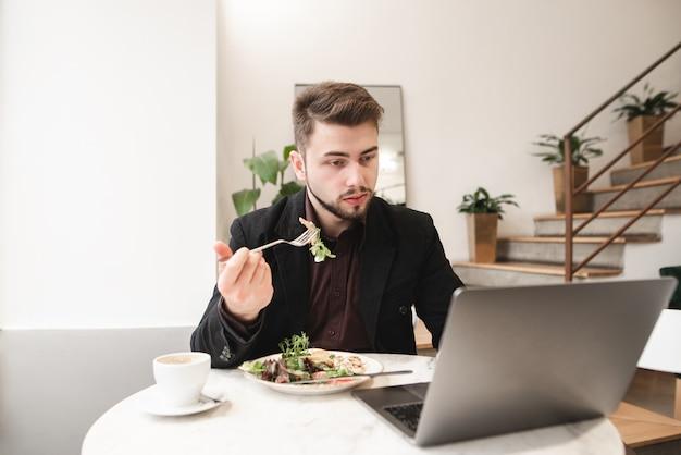 Biznesowy mężczyzna używa laptopu na lunch w kawiarni.