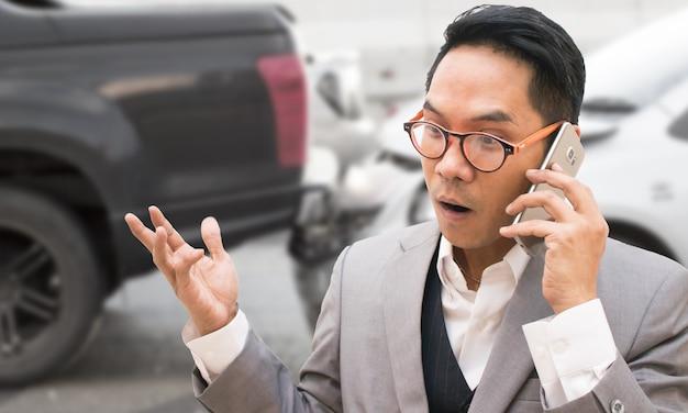 Biznesowy mężczyzna używa mądrze telefon i dzwoni ubezpieczenie samochodu.