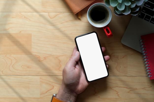 Biznesowy mężczyzna używa telefon komórkowego na drewnianym workspace