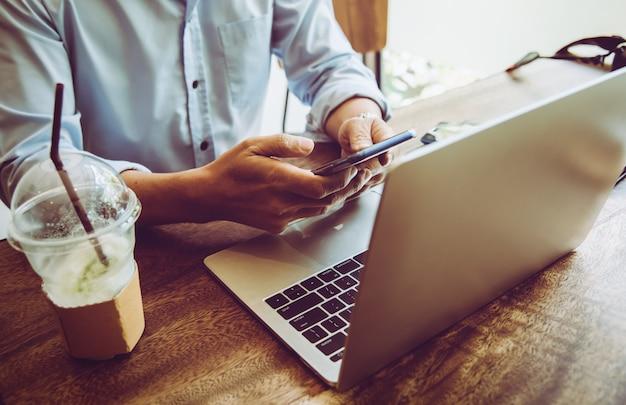 Biznesowy mężczyzna używa wiszącą ozdobę i laptop znajduje pracę w sklep z kawą