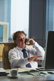Biznesowy mężczyzna w biurze otrzymywa rozmowę telefonicza