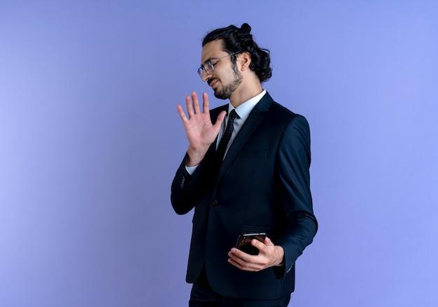 Biznesowy mężczyzna w czarnym garniturze i okularach robi gest obrony przed swoim smartfonem z obrzydzonym wyrazem twarzy stojącej nad niebieską ścianą