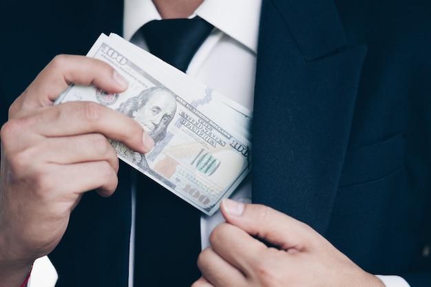 Biznesowy mężczyzna w kostiumach otrzymywa dużą ilość usa banknoty jako łapówka