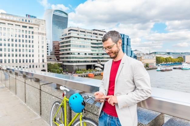 Biznesowy mężczyzna w londyn dojeżdżać do pracy rowerem i pisać na maszynie na jego smartphone