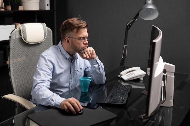 Biznesowy mężczyzna w szkłach pracuje w biurze przy komputeru stołem i pije kawę od jaskrawej filiżanki