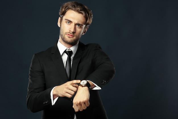 Biznesowy mężczyzna wskazuje przy jego zegarkiem