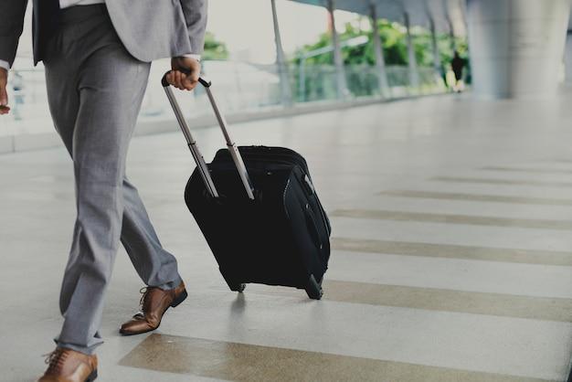 Biznesowy mężczyzna z bagażem iść na podróży służbowej