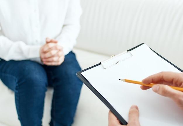 Biznesowy mężczyzna z dokumentami i kobieta siedzi na kanapie w jasnym pokoju. wysokiej jakości zdjęcie