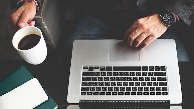 Biznesowy mężczyzna z laptopem i filiżanką kawy