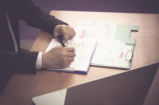 Biznesowy mężczyzna z pióra writing notatką na papierze