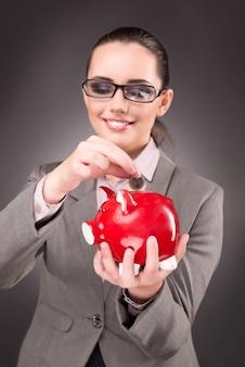 Biznesowy pojęcie z bizneswomanem i prosiątko bankiem