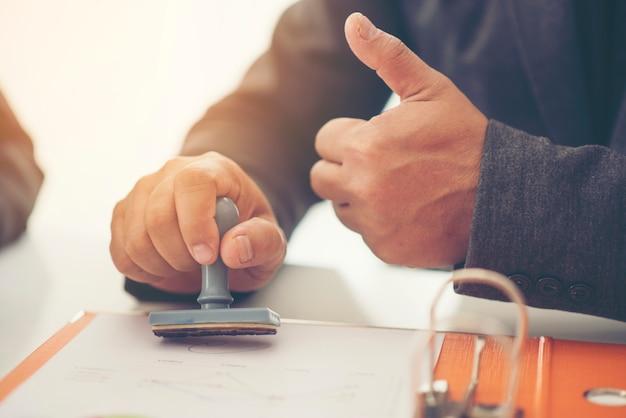 Biznesowy ręki kładzenia znaczek na dokumencie, zamyka up