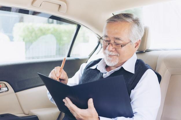 Biznesowy senior w kostiumu pracującym podpisuje kontrakt zatwierdzającego w jego samochodzie, starszy biznesowy sukces