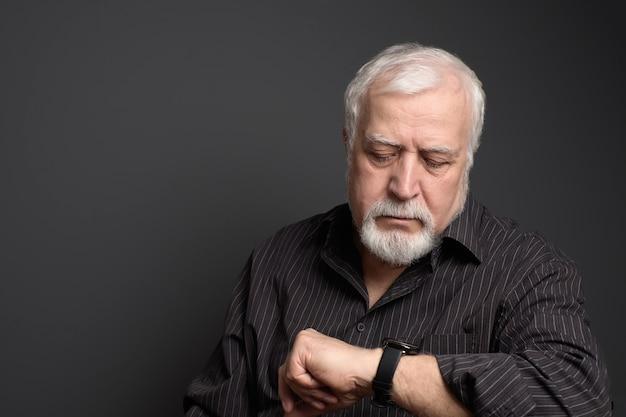 Biznesowy siwy mężczyzna, patrząc na elegancki zegarek, czas to pieniądz