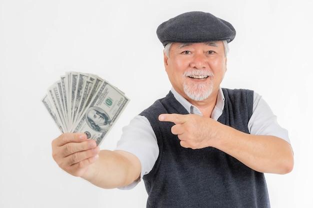 Biznesowy starszy bogacz trzymający pieniądze rachunki w dolarach amerykańskich i wskazujący pieniądze w ręku na białym tle na białym tle, koncepcja dla starszego biznesu sukcesu