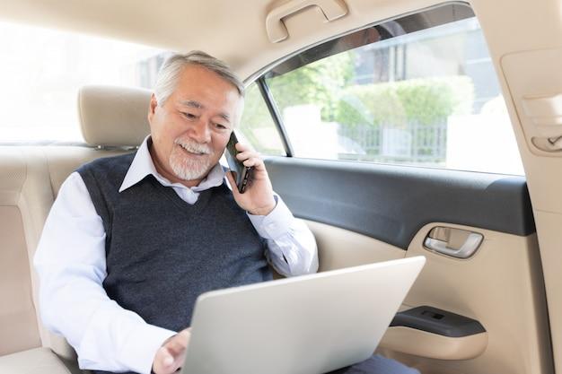 Biznesowy starszy bogaty człowiek stocker gracz w kostiumu pracuje z laptopem w jego samochodzie