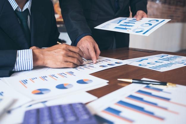 Biznesowy urzędnik pomaga sprawdzać pieniężnych dokumenty i pieniężne mapy w biurze