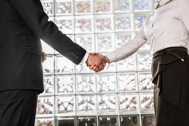 Biznesowy uścisk dłoni. biznesmen i bizneswoman drżenie rąk w biurze