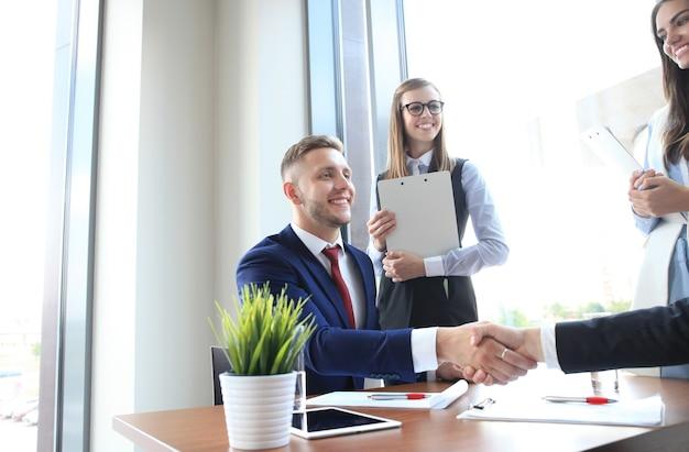 Biznesowy uścisk dłoni. dwóch biznesmenów, ściskając ręce w biurze.