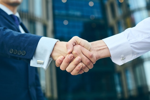 Biznesowy uścisk dłoni na świeżym powietrzu przed budynkiem biurowym. koncepcja spotkania partnerstwa. udani biznesmeni uścisk dłoni po dobrej transakcji.
