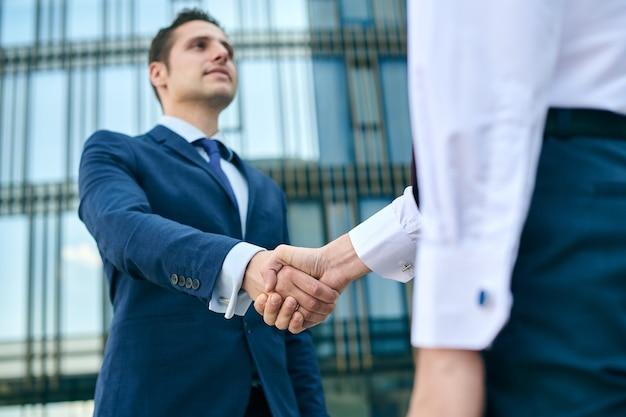 Biznesowy uścisk dłoni na tle centrum biurowego. koncepcja spotkania partnerstwa. pomyślni biznesmeni uścisk dłoni po dobrej transakcji.