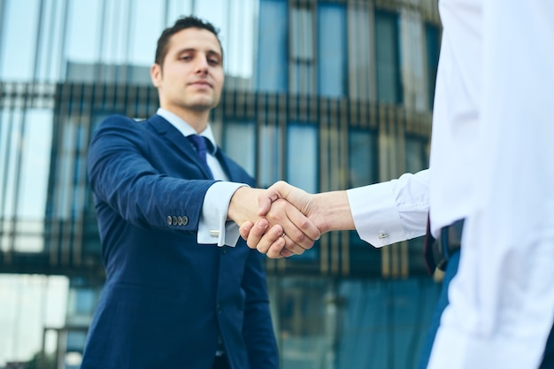 Biznesowy uścisk dłoni na zewnątrz budynku biurowego. koncepcja spotkania partnerstwa. pomyślni biznesmeni uścisk dłoni po dobrej transakcji. niski widok