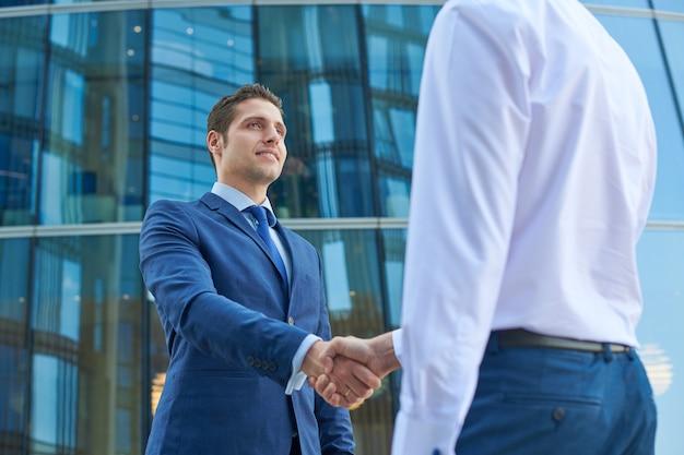 Biznesowy uścisk dłoni poza centrum biznesowym. koncepcja spotkania partnerstwa. pomyślni biznesmeni uścisk dłoni po dobrej transakcji.
