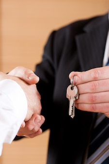 Biznesowy uścisk dłoni z dawaniem kluczy