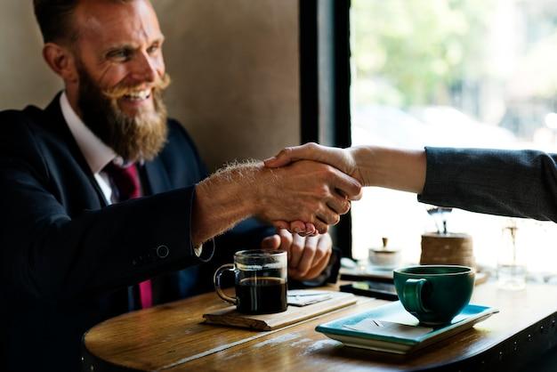 Biznesowy zgoda uścisk dłoni przy sklep z kawą