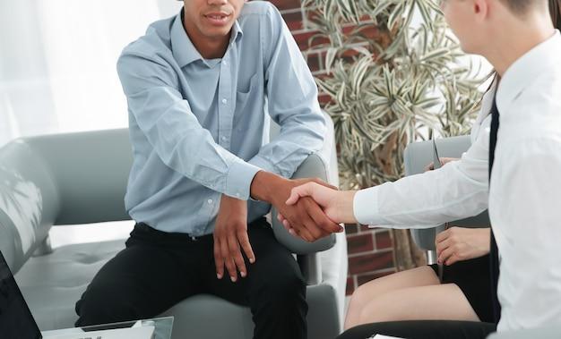 Biznesowych partnerów finansowych uścisk dłoni w biurze.