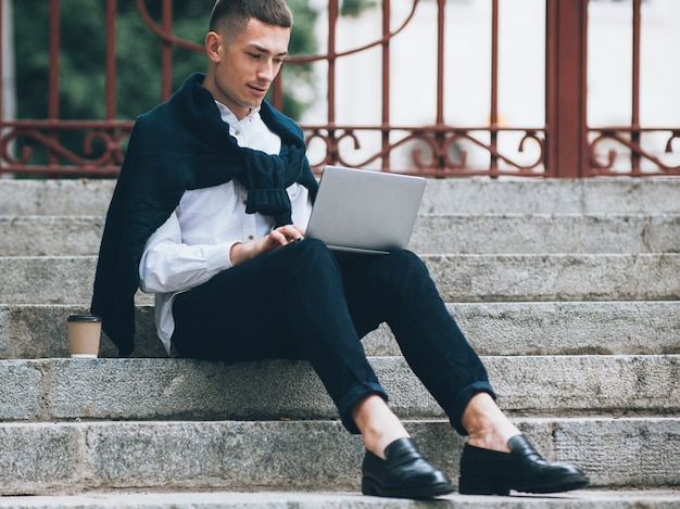 Biznesu online. nowoczesna technologia. stylowy mężczyzna siedzący na schodach pracuje na laptopie.