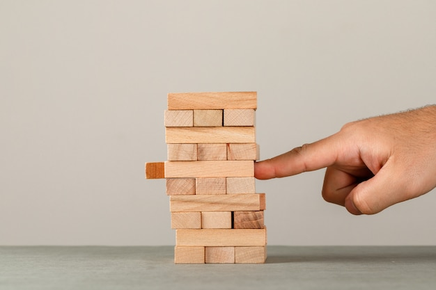 Biznesu, ryzyka i zarządzania pojęcie na popielatym i białym ściennym bocznym widoku. pchanie palcem drewniana wieża blokowa.