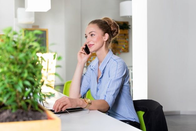 Biznesu, technologii i zieleni biurowy pojęcie, - młody pomyślny bizneswoman opowiada na telefonie przy biurem z laptopem. piękna kobieta używa pastylka komputer.