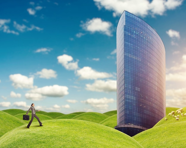 Bizneswoman biegnie do budynku na trawiastych wzgórzach