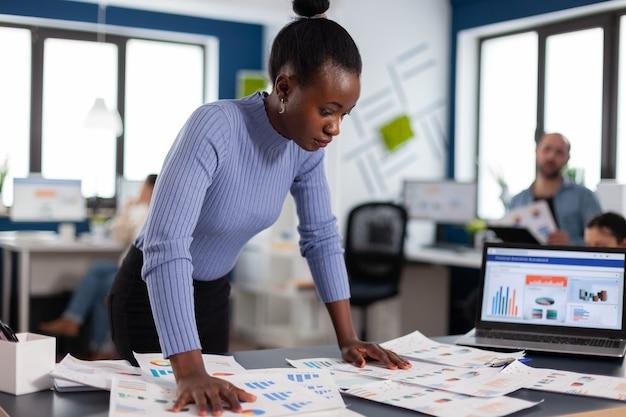 Bizneswoman czarny sprawdzający pracę wieloetnicznych kolegów w agencji startowej. zróżnicowany zespół ludzi biznesu analizujących z komputera raporty finansowe firmy. start up sukcesy korporacyjne