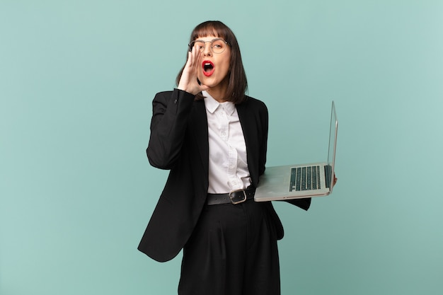 Bizneswoman czuje się szczęśliwa, podekscytowana i pozytywna, wydając wielki okrzyk z rękami przy ustach, wołając