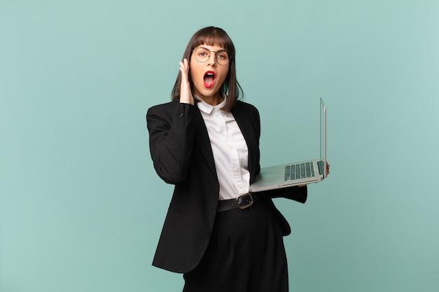 Bizneswoman czuje się szczęśliwa, podekscytowana i zaskoczona, patrząc w bok z obiema rękami na twarzy