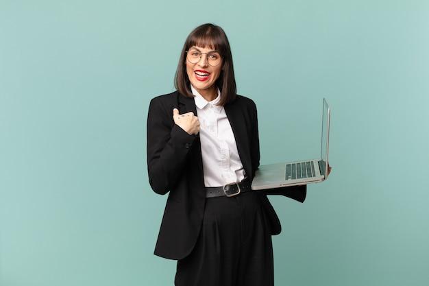 Bizneswoman czuje się szczęśliwa, zaskoczona i dumna, wskazując na siebie z podekscytowanym, zdumionym spojrzeniem
